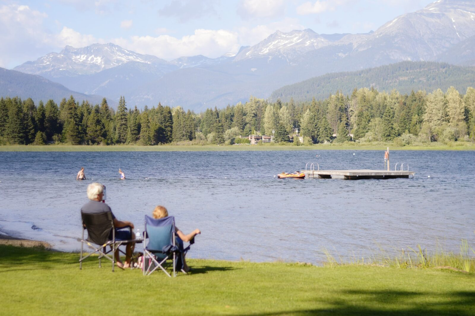 older retired couple on bench next to lake